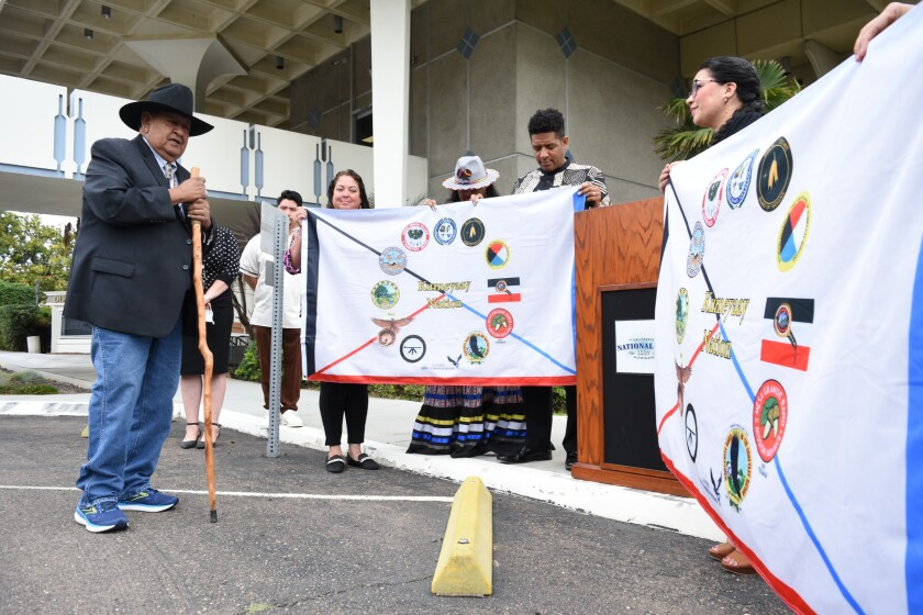 Jamul Indian Village Councilmember Jesse Pinto Sr. offers a blessing of two Kumeyaay flags in National City.