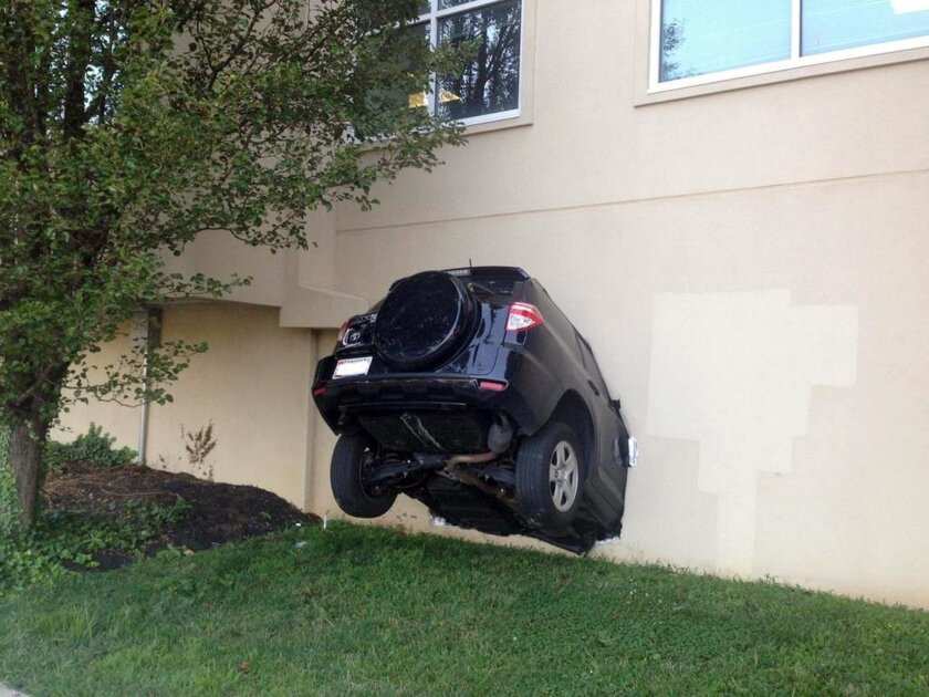 In this photo provided by the Baltimore County Police, an SUV hangs out of the side of a building that houses county offices after its driver drove into the building, injuring three people, Thursday, July 31, 2014, in Towson, Md. The driver was charged with failure to reduce speed to avoid a collis