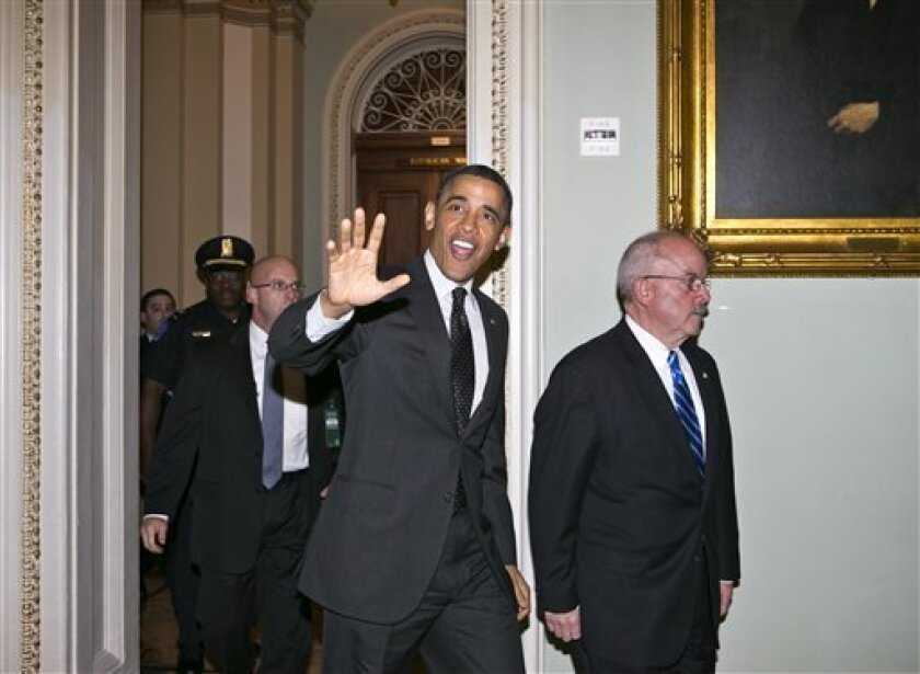 President Barack Obama, escorted by Senate Sergeant at Arms Terry Gainer, waves as he arrives on Capitol Hill in Washington, Tuesday, March 12, 2013, to visit with Senate Democrats in the first of four meetings with lawmakers this week to discuss the budget. (AP Photo/J. Scott Applewhite)
