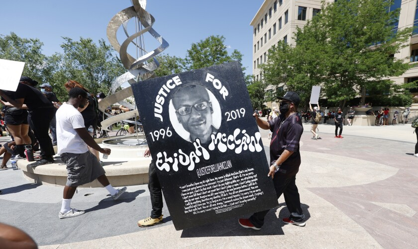 Activists carry a sign during a protest over the death of Elijah McClain on June 27 in Aurora, Colo.