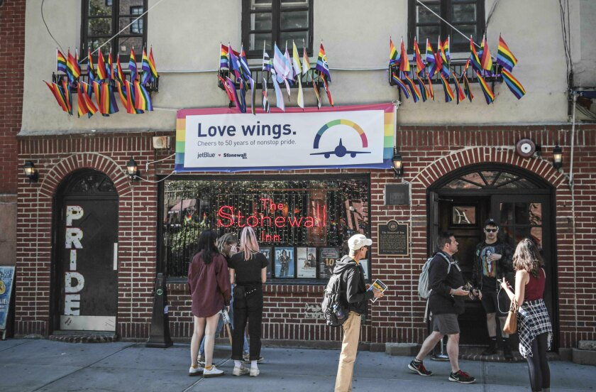 FILE - In this Monday, June 3, 2019, file photo, Pride flags and colors display on the Stonewall Inn bar, marking the site of 1969 riots that followed a police raid of the bar's gay patrons, in New York. The Stonewall Inn's owners say they won't serve certain beers at the famous LGBT bar during Pride weekend to protest manufacturer Anheuser-Busch's political contributions to some politicians who have supported anti-LGBT legislation. (AP Photo/Bebeto Matthews, File)