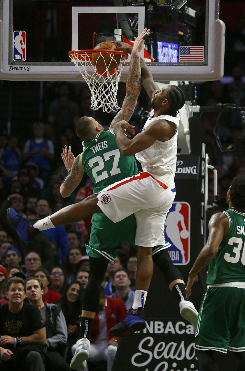 LOS ANGELES, CALIF. - NOV. 20, 2019. Clippers forward Kawehi Leonard throws down a dunk against Celtics forward Daniel Theis in thje fourth quarter at Staples Center in Los Angeles on Wednesday might, Nov. 20, 2019. (Luis Sinco/Los Angeles Times)