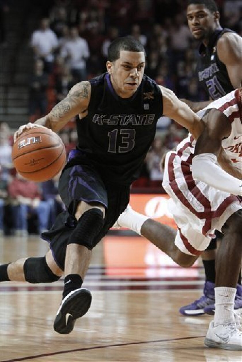 Kansas State guard Angel Rodriguez (13) drives to the basket around Oklahoma guard Buddy Hield (3) during the first half of an NCAA college basketball game in Norman, Okla., Saturday, Feb. 2, 2013. (AP Photo/Alonzo Adams)