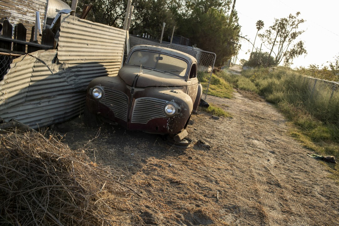A vintage automobile sits on blocks in a dusty alley.