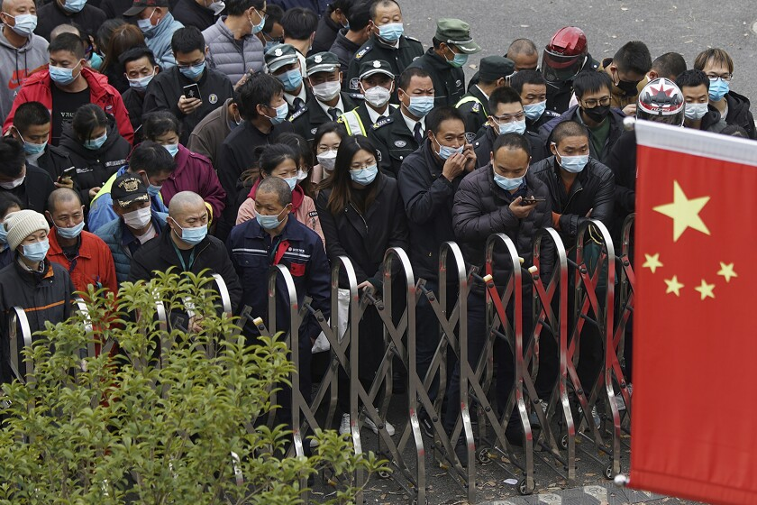Masked airport workers wait behind a metal barrier for coronavirus testing