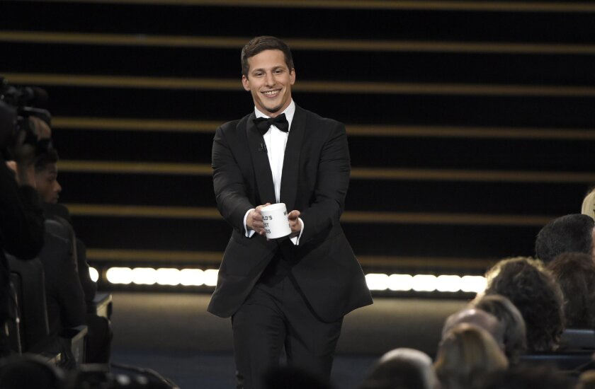 Host Andy Samberg prepares to present a coffee mug to Lorne Michaels at the 67th Primetime Emmy Awards on Sunday, Sept. 20, 2015, at the Microsoft Theater in Los Angeles. (Photo by Chris Pizzello/Invision/AP)