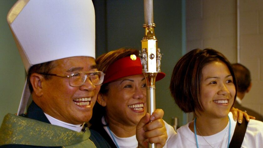 The first Vietnamese–American bishop, Dominic Luong poses with parishioners after a 2003 Mass at UC Irvine