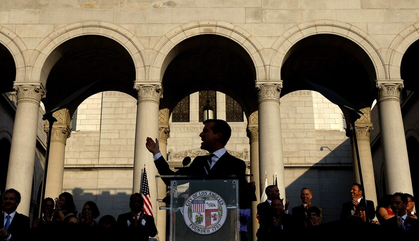 L.A. Mayor Eric Garcetti speaks at a lectern on the steps of City Hall in front of a line of people