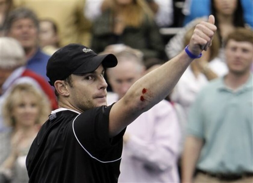 Andy Roddick's scraped elbow is visible as he salutes the crowd after beating Lleyton Hewitt, of Australia, in a quarterfinal match at the Regions Morgan Keegan Championships tennis tournament Friday, Feb. 18, 2011, in Memphis, Tenn. Roddick scraped his elbow when he fell while returning a shot. Roddick won 4-6, 6-3, 6-4. (AP Photo/Mark Humphrey)