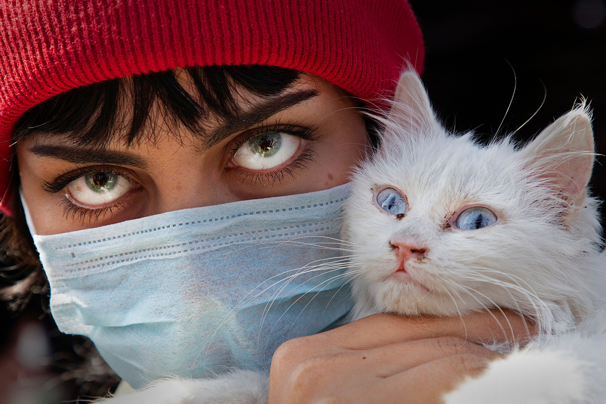 IRAQ: A woman wearing a protective mask and colored contact lenses holds her cat as she poses for a picture during a protest against corruption in the Iraqi government in the southern city of Basra on Feb. 27.