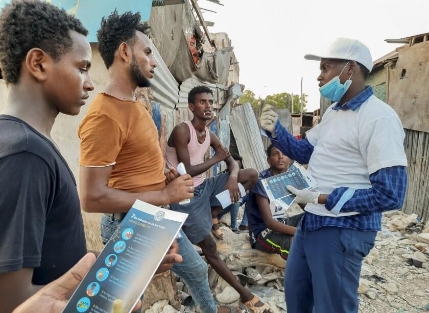 Stranded Ethiopian migrants in Bosaso, Somalia, receive brochures about the coronavirus.