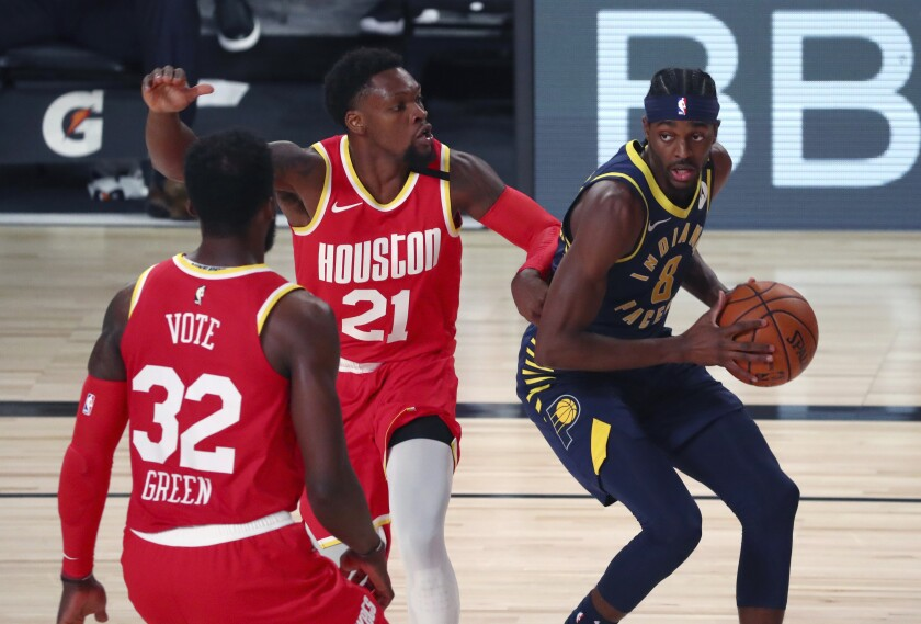 Indiana Pacers forward Justin Holiday (8) drives to the basket against Houston Rockets guard Michael Frazier (21) and forward Jeff Green (32) during the second half of an NBA basketball game Wednesday, Aug. 12, 2020, in Lake Buena Vista, Fla. (Kim Klement/Pool Photo via AP)