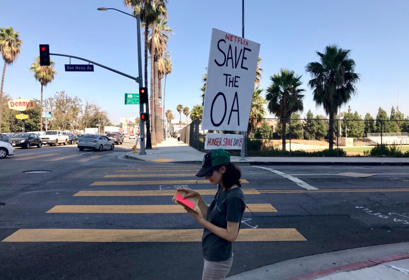 """Emperial Young with her """"Save the OA"""" sign, standing on the corner of Sunset Blvd. and Van Ness in Hollywood outside Netflix."""
