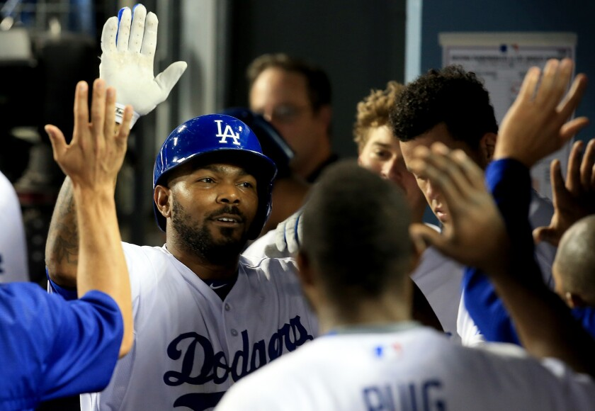 Dodgers second baseman Howie Kendrick is congratulated by teammates after hitting a solo home run against the Diamondbacks in the seventh inning of Tuesday's game at Dodger Stadium. TV ratings for the game soared in the first telecast of the team-owned SportsNet LA channel on Charter Communications systems in the Los Angeles region.