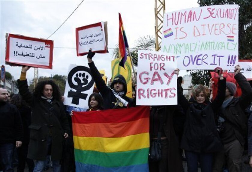 In this Sunday, Feb. 22, 2009 picture, protesters carry banners during a sit-in for gays and lesbians in Beirut. In February, about two dozen gays and lesbians held a rare sit-in on Beirut's major intersection of Sodeco to protest what they called the beating of two gay men by two plainclothes police. Police officials denied the men were beaten their officers. (AP Photo/Hussein Malla)