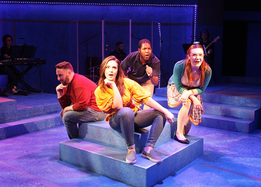 Four singers sitting on a raised platform look into the distance with expressions of surprise and hopefulness.
