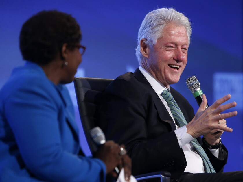 "Former President Clinton laughs as he answers a question from Gwen Ifill of ""PBS NewsHour"" regarding Republicans' questioning of wife Hillary Rodham Clinton's health, at the 2014 Fiscal Summit organized by the Peter G. Peterson Foundation in Washington."
