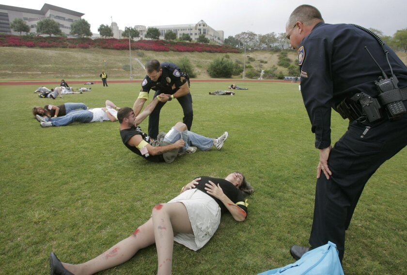 Carlsbad police officers perform checks for injuries among volunteers who acted as victims of a radioactive bomb blast at Cal State San Marcos on Tuesday during a countywide exercise in preparedness for a terrorist attack. The Port of San Diego also came under a mock attack.