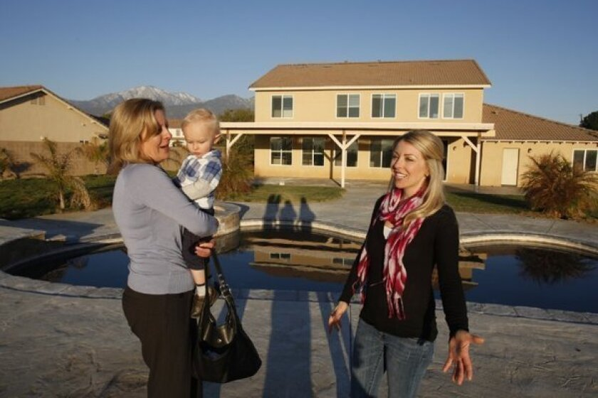 Shannon Bridgewater, right, with her son Brayden, and real estate agent Carey Chenoski check out a house in Yucaipa this year. The Inland Empire is reemerging as a home-building hot spot.