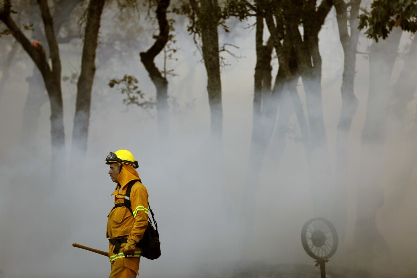 Volunteer firefighter Michael Simon is surrounded by smoke while working a fire in the Oakmont community along Highway 12