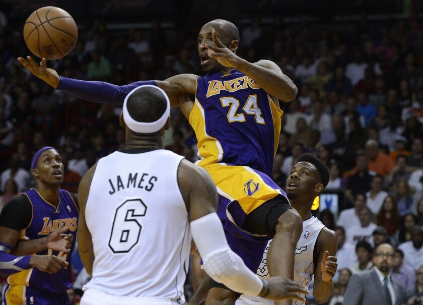 Kobe Bryant snags the ball against the LeBron James and the Miami Heat.
