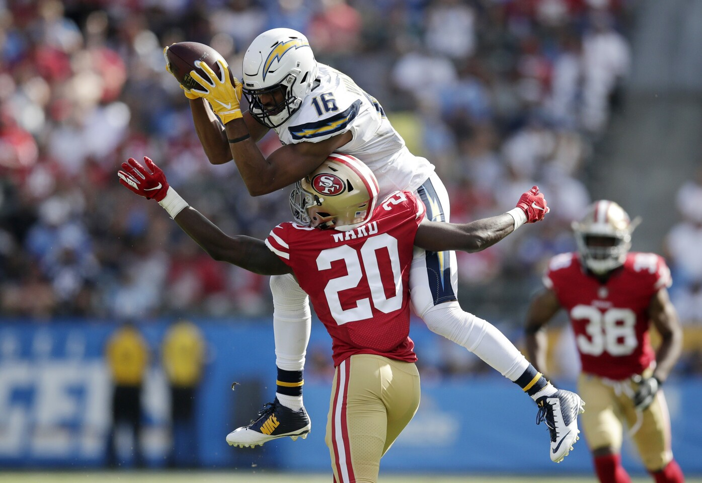Los Angeles Chargers wide receiver Tyrell Williams, top, makes a catch while under pressure from San Francisco 49ers defensive back Jimmie Ward during the second half of an NFL football game, Sunday, Sept. 30, 2018, in Carson, Calif.