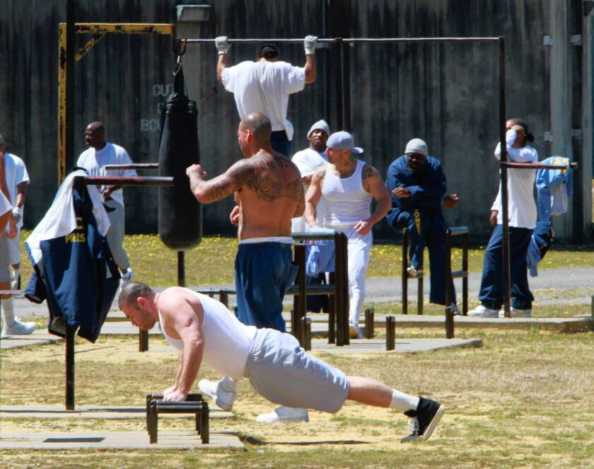Inmates exercise in the general population yard at Pelican Bay State Prison. California prison population reports show crowding has fallen below a court-ordered cap for the first time.