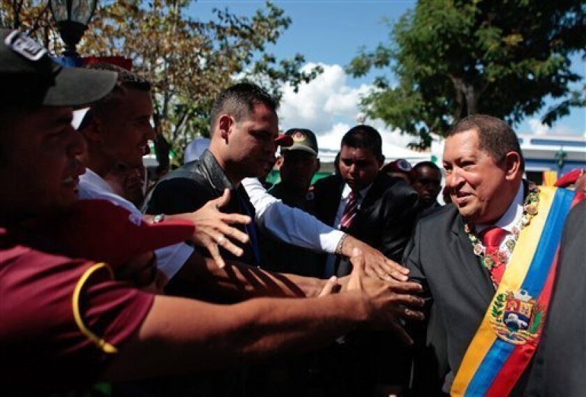 In this photo provided by Miraflores Press Office, Venezuela's President Hugo Chavez, right, greets supporters as he arrives for the 193 anniversary of the Agostura Congress in Ciudad Bolivar, Venezuela, Wednesday Feb. 15, 2012. Chavez accused the opposition's presidential candidate Wednesday of concealing his ideological leanings and trying to mislead government supporters that he shares some of the president's left-leaning ideals. Venezuela will hold its presidential election on Oct. 7. (AP Photo/Miraflores Press Office)