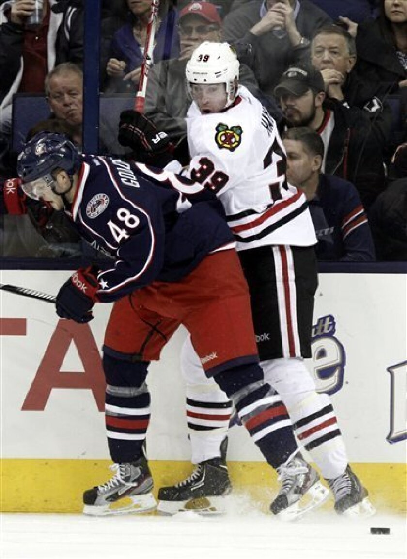 Columbus Blue Jackets' Cody Goloubef, left, and Chicago Blackhawks' Jimmy Hayes work for the puck in the second period of an NHL hockey game in Columbus, Ohio, Thursday, March 14, 2013. (AP Photo/Paul Vernon)
