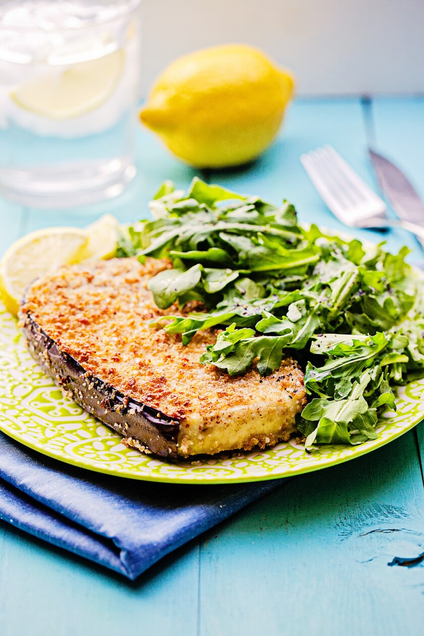 Thick-cut eggplant is breaded in cheesy panko and served with a side of fresh arugula salad.