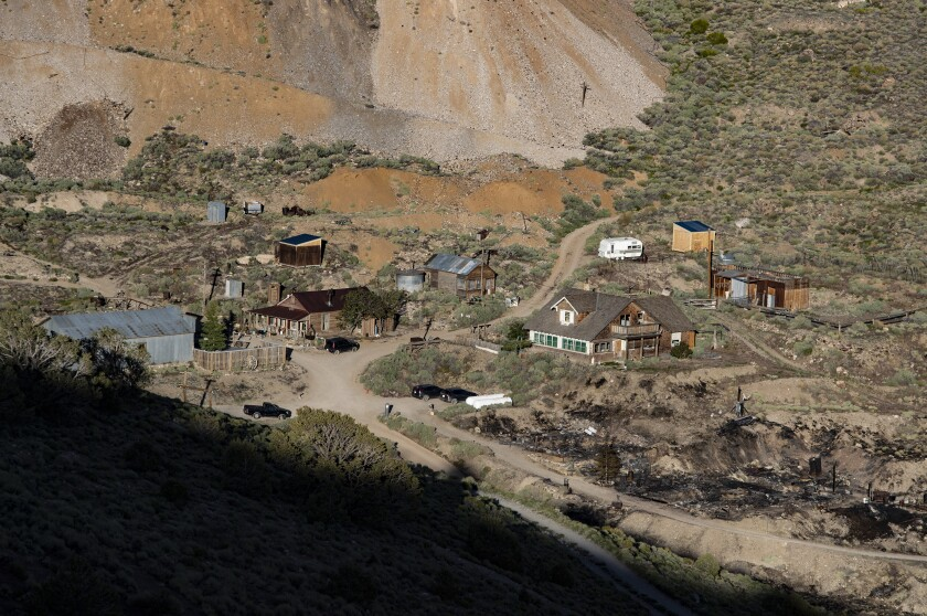Rustic buildings on a brushy slope below mine tailings near the blackened ground where Cerro Gordo's  American Hotel burned.