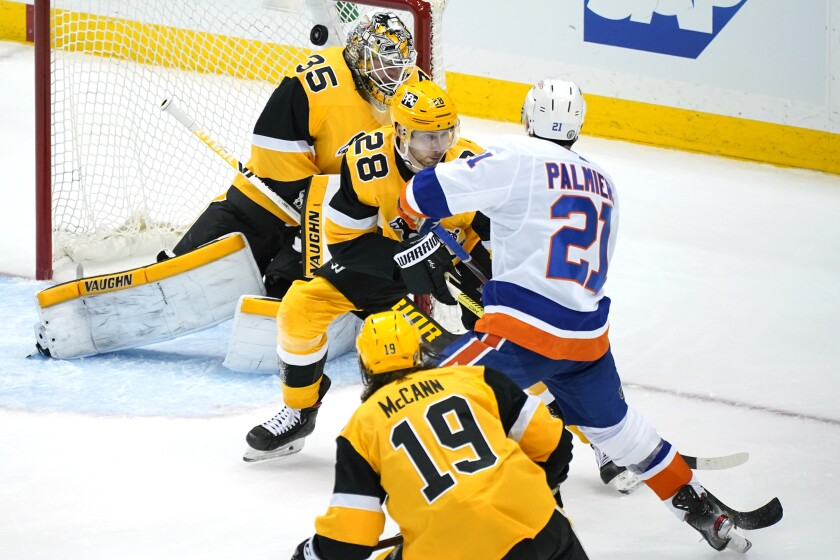 New York Islanders' Kyle Palmieri (21) puts a shot over Pittsburgh Penguins goaltender Tristan Jarry (35) with Marcus Pettersson (28) defending for the game-winning goal in overtime in Game 1 of an NHL hockey Stanley Cup first-round playoff series in Pittsburgh, Sunday, May 16, 2021. The Islanders won 4-3. (AP Photo/Gene J. Puskar)