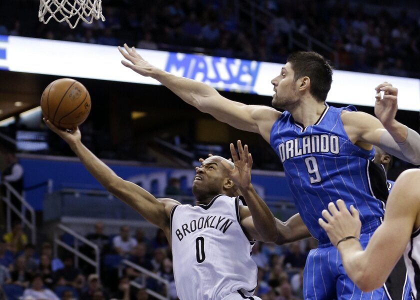 Brooklyn Nets' Jarrett Jack (0) goes in to shoot as Orlando Magic's Nikola Vucevic (9) tries to defend during the first half of an NBA basketball game, Friday, Jan. 2, 2015, in Orlando, Fla. (AP Photo/John Raoux)