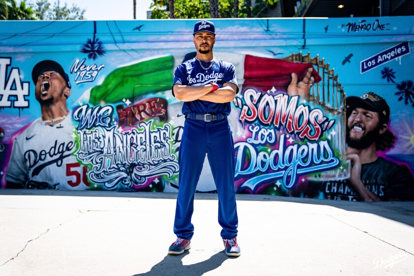 Dodgers' Mookie Betts poses in front of street art.