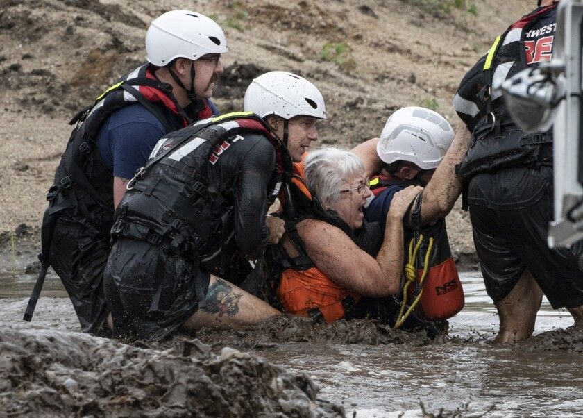 A team of Northwest Fire District firefighters walk a woman away from a stranded pickup truck in the Cañada del Oro Wash north of Tucson, Ariz., on Tuesday, Aug. 10, 2021. Firefighters rescued three people from one of two vehicles in the wash, swollen with runoff after an early morning downpour dumped nearly two-inches upstream. (Rick Wiley/Arizona Daily Star via AP)
