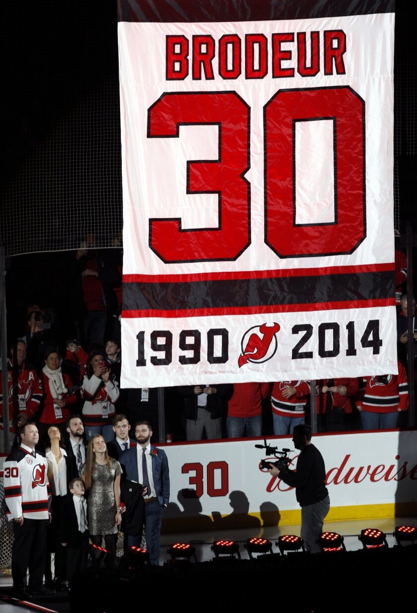 Former New Jersey Devils star goalie Martin Brodeur, left, looks on with his family as the Devils retire Brodeur's number 30 jersey before an NHL hockey game against the Edmonton Oilers Tuesday, Feb. 9, 2016, in Newark, N.J. (AP Photo/Mel Evans)