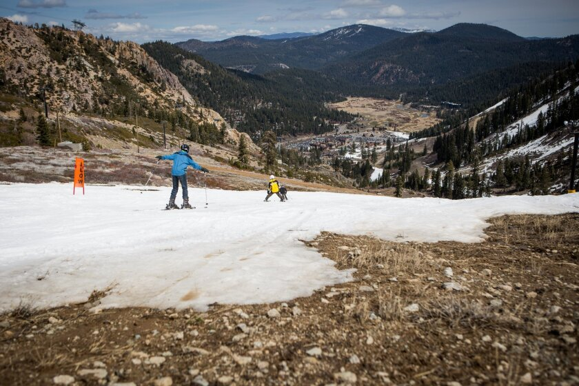 Skiers make their way around patches of dirt at Squaw Valley Ski Resort.