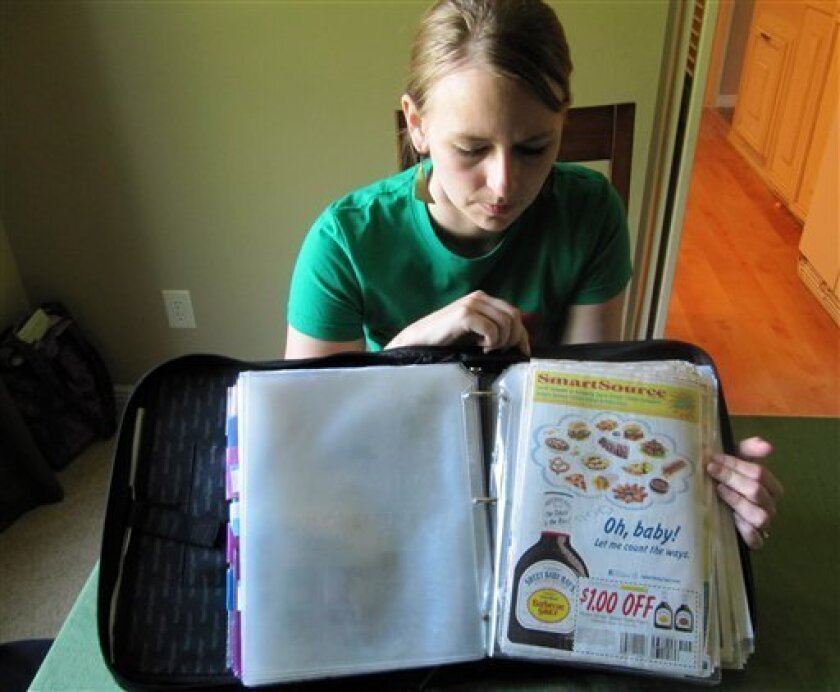 In this photo taken Tuesday, June 28, 2011, Monica Knight, a dental hygienist and mother of two, shows her coupon binder at her home in Boise, Idaho. Knight, a used to spend spent $600 a month on groceries. Thanks to extreme couponing she's down to $100-150 a month. (AP Photo/Jessie L. Bonner)