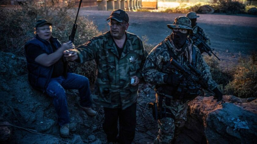 """Jim Benvie, center, and other members of the United Constitutional Patriots patrol the U.S.-Mexico border in Sunland Park, N.M. Benvie said the militia group was assisting a """"stressed and overstrained Border Patrol."""""""