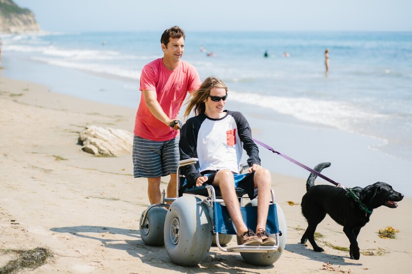 Jon Menzies pushes Sean Goral in a beach wheelchair alongside his dog Spirit in Santa Barbara.
