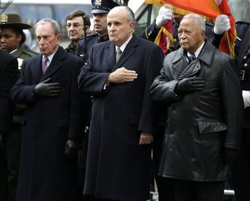 New York City Mayor Michael Bloomberg, left, and former New York City Mayors Rudolph Giuliani, center, and David Dinkins put their hands over their hearts as a casket containing the body of former New York City Mayor Ed Koch leaves a synagogue after his funeral in New York, Monday, Feb. 4, 2013. Koch was remembered as the quintessential New Yorker during a funeral that frequently elicited laughter, recalling his famous one-liners and amusing antics in the public eye. (AP Photo/Seth Wenig)