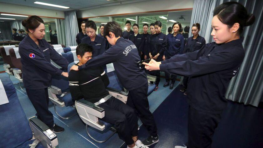 Crew members of Korean Air receive training in handling unruly passengers in a mock cabin in Seoul on Dec. 27, 2016.