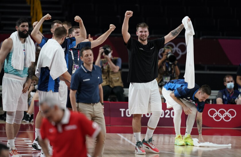 Slovenia's Luka Doncic (77), right, and teammates celebrate on the bench during men's basketball preliminary round game against Japan at the 2020 Summer Olympics, Thursday, July 29, 2021, in Saitama, Japan. (AP Photo/Charlie Neibergall)