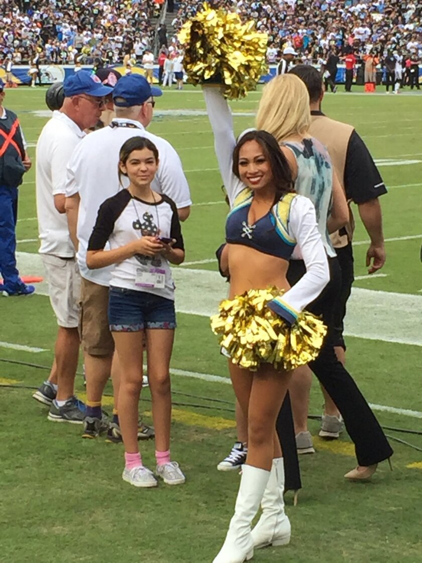Emily Newton, left, with a Chargers Girl on the Chargers sidelines. Courtesy photo