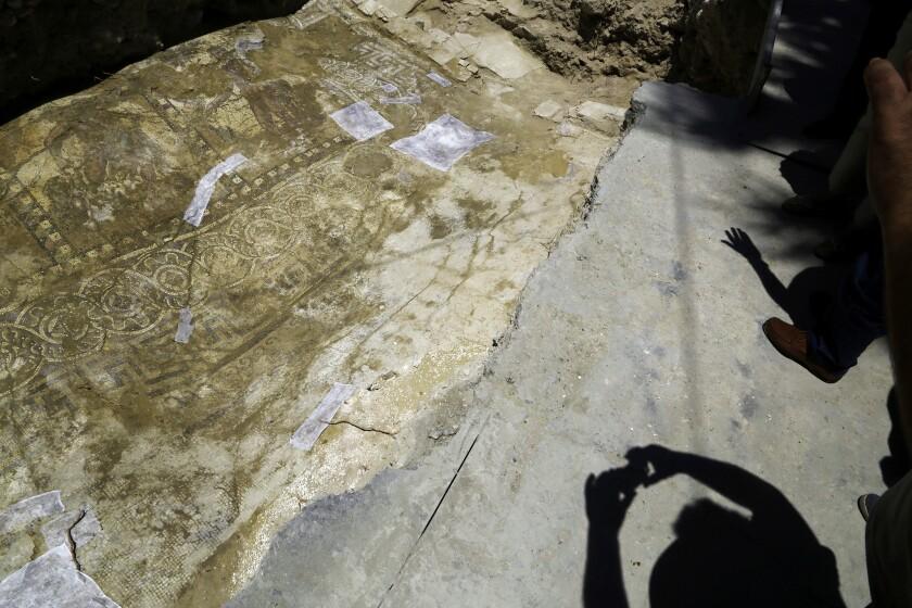 Periodistas y arqueólogos proyectan sombras sobre un mosaico con la representación de Hércules en la ciudad de Larnaca, al sur de Chipre. (AP Foto/Petros Karadjias)