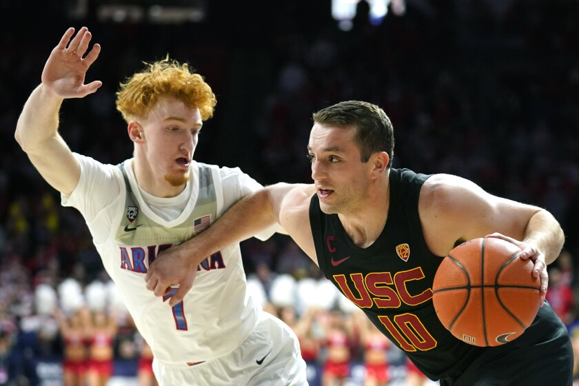 USC guard Quinton Adlesh drives against Arizona guard Nico Mannion during the first half of a game Feb. 6 at McKale Memorial Center.