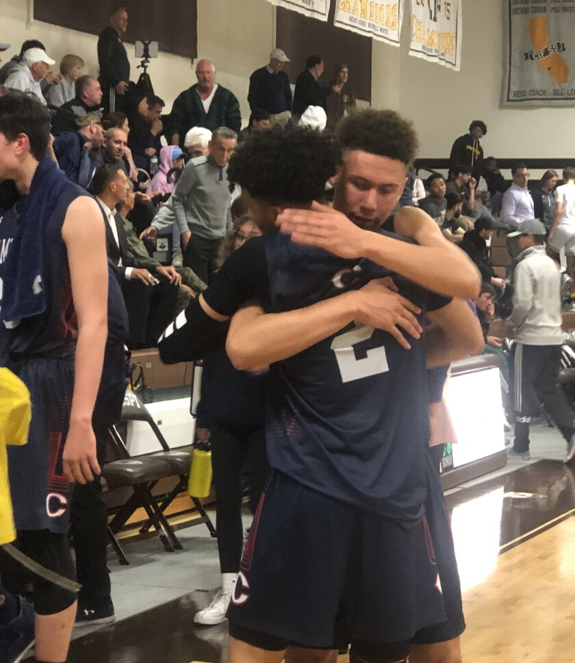 Kenneth Simpson Jr. (No. 2) receives hug from teammate Keith Higgins Jr. after scoring 41 points on Wednesday to help Chaminade defeat St. Francis 83-78 in the semifinals of the Mission League tournament.
