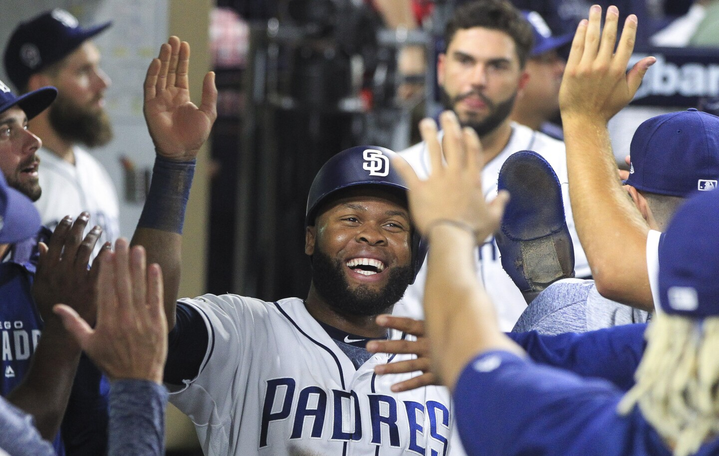 The Padres' Manuel Margot is congratulated in the dugout after he scored on a two-run single by Wil Myers in the seventh inning against the Cubs at Petco Park on Wednesday , September 11, 2019 in San Diego, California.