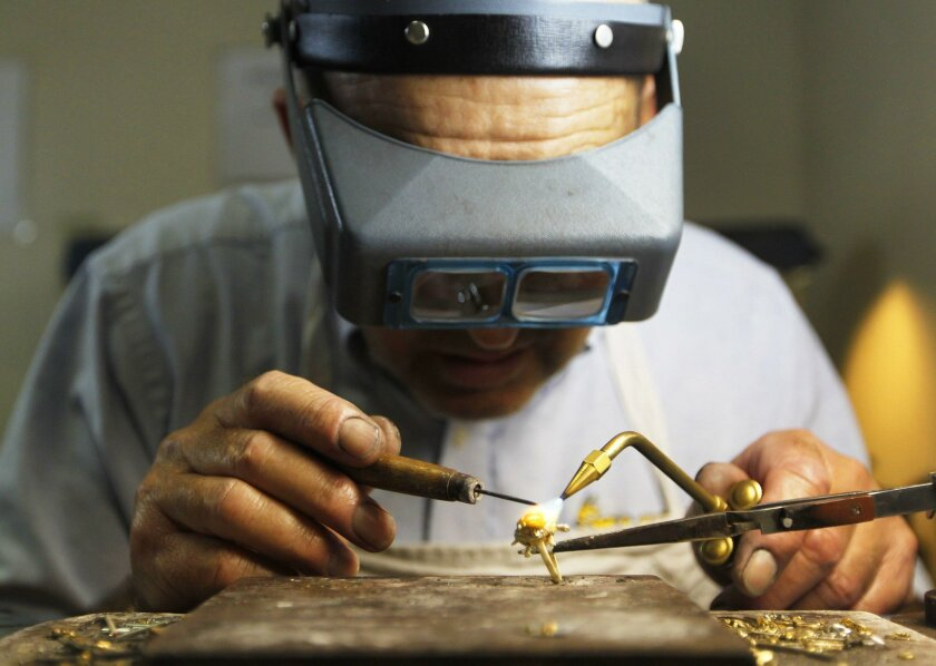 Jeweler Emile Jossi works on a ring at CashCo Pawn, which gives loans to small-business owners who have collateral.