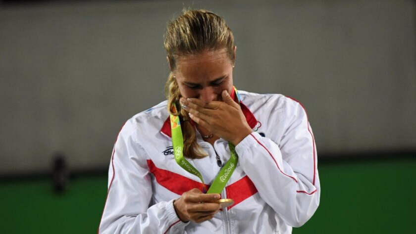 Monica Puig of Puerto Rico gets emotional while holding her gold medal for women's tennis during the podium ceremony on Aug. 13.